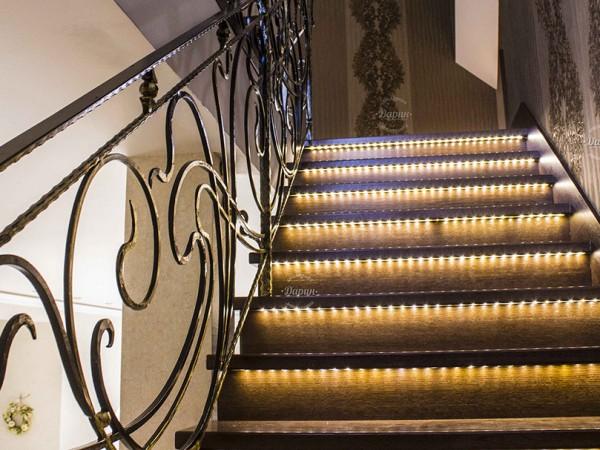 Дизайн лестницы в частном загородном доме: ручная ковка, дуб с подсветкой.
