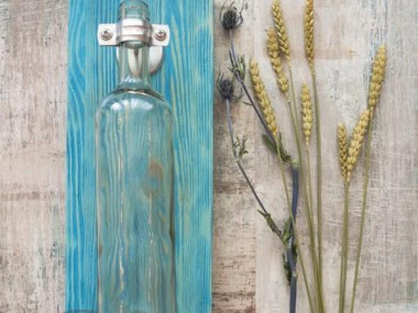 Подвесная ваза из стеклянной бутылки на белой подложке из массива дерева